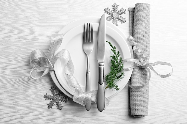 Christmas serving cutlery on plate and napkin over light wooden table