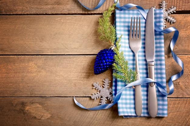 木製の背景にナプキンとカトラリーを提供するクリスマス