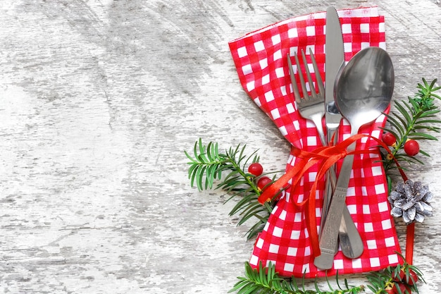 Christmas serving cutlery with napkin on white wooden background