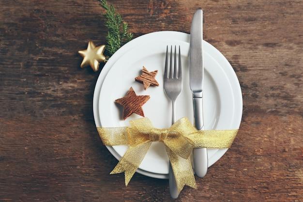 Рождественские столовые приборы с тарелкой на деревянном фоне