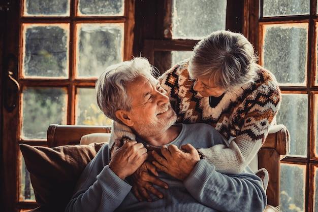 クリスマスの季節の休日の成熟したカップルの笑顔と愛を楽しんでいます