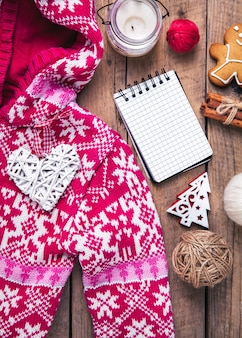 Christmas set. warm blanket, sweater, candle, notebook, spices, cinnamon, pine cones, heart on the wooden