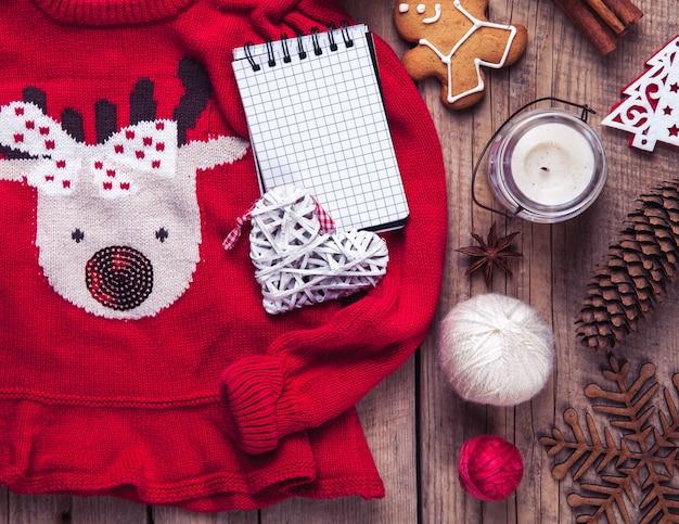 クリスマスセット。暖かい毛布、鹿、キャンドル、ノート、スパイス、シナモン、松ぼっくり、木製のテーブルの上の心のセーター