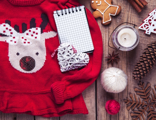 Christmas set. warm blanket, sweater with a deer, candle, notebook, spices, cinnamon, pine cones, heart  on the wooden table