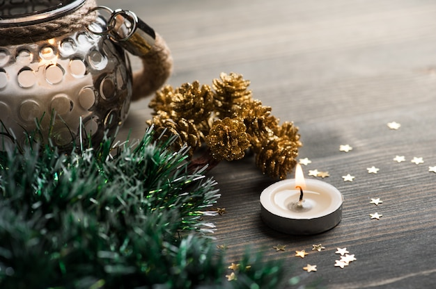 Christmas setting with golden pines, lit candles and stars
