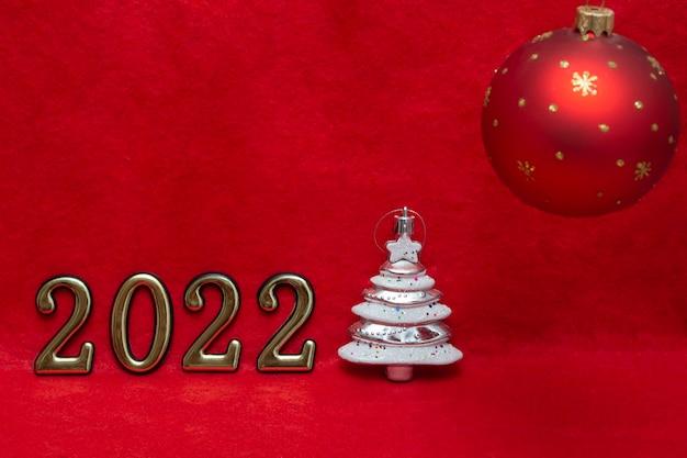 クリスマスの光沢のある赤いボールと赤い背景に金色の数字と銀の木。 2022年の新年がもうすぐ始まります。はがきのレイアウト、パッケージ。バナー