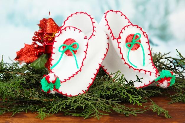 明るい背景のテーブルに装飾が施されたクリスマスシューズ