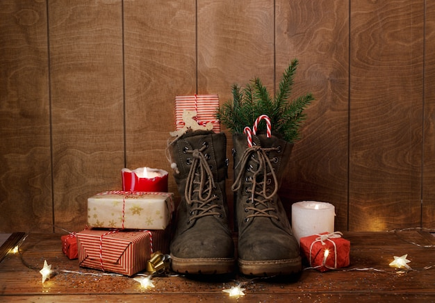 Christmas shoes on a wooden background around gifts, burning candles