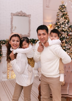 クリスマスの撮影のコンセプト、木で居心地の良いセーターで2人の子供と幸せなアジアの家族