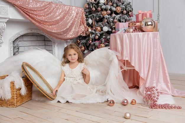 Новогодняя съемка милой маленькой девочки в студии с крыльями