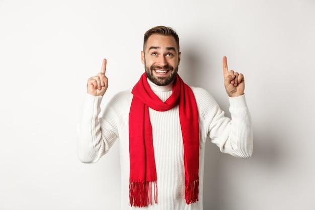 クリスマスの買い物と冬の休日のコンセプト。指を上に向けて、コピースペースで興奮して見て、白い背景の上に立って、赤いスカーフで幸せなひげを生やした男
