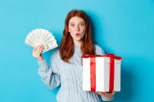 Natale e concetto di acquisto. eccitata ragazza rossa che guarda l'obbiettivo, tenendo in mano un grande regalo di capodanno e dollari, comprando regali, in piedi su sfondo blu.