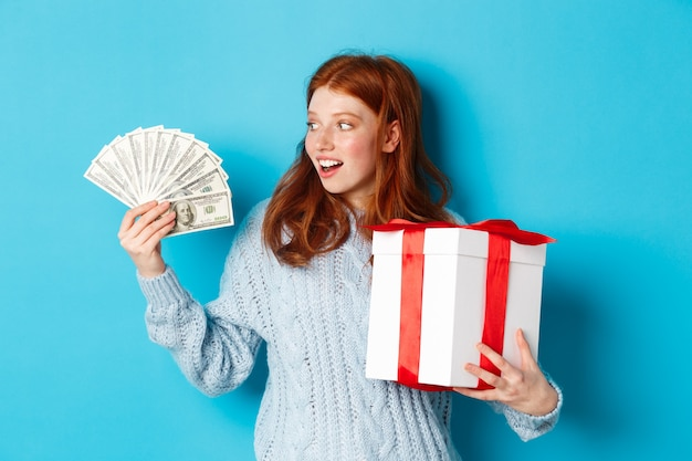 Christmas and shopping concept. excited redhead girl looking at dollars, holding big new year gift, buying presents, standing over blue background.
