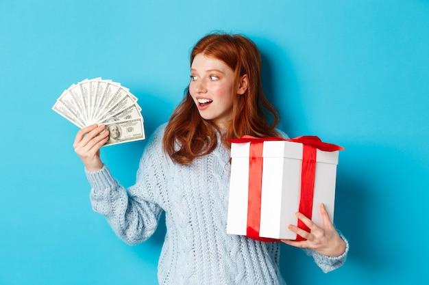 Natale e concetto di acquisto. eccitata ragazza rossa che guarda i dollari, tiene in mano un grande regalo di capodanno, compra regali, sta in piedi su sfondo blu