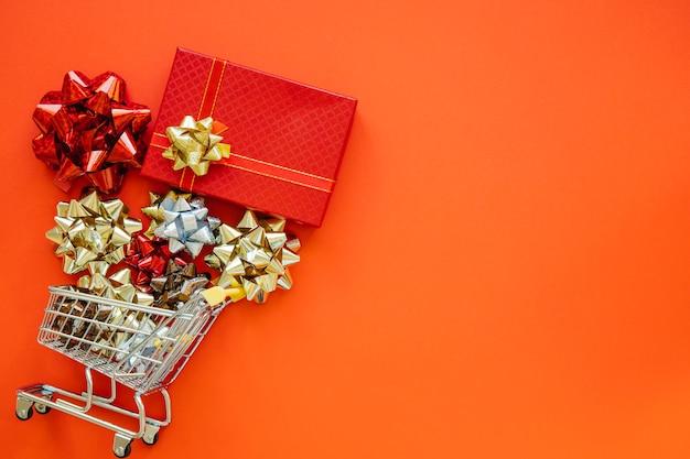 Концепция рождественских покупок с подарком и тележкой