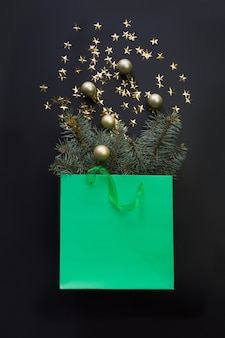 Christmas shopping green paper bag with golden decor and fir tree branches.