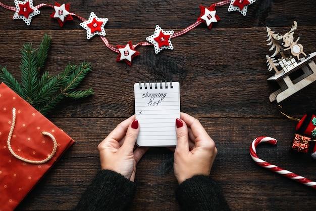 クリスマスの買い物リスト予算のクリスマスの買い物クリスマスのお金を節約するためのヒント女性の手