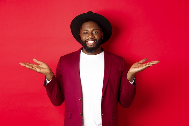 Christmas shopping and people concept. handsome african american man smiling, spread hands sideways, showing promo offers on copy space, red background