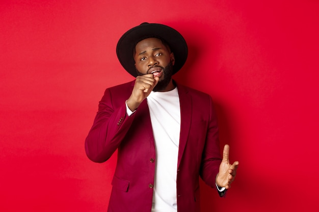 Christmas shopping and people concept. handsome black male model in party outfit singing in invisible microphone, looking passionate at camera, red background