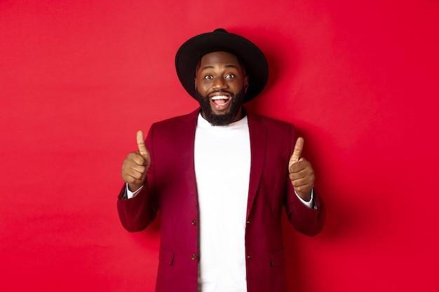 Shopping di natale e concetto di persone. un bell'uomo di colore che sorride soddisfatto, mostra il pollice in su, mi piace e concorda, approva qualcosa, in piedi su sfondo rosso.