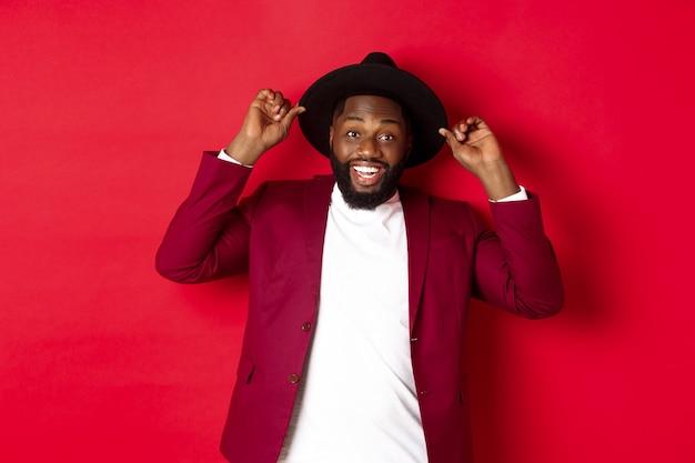 Shopping di natale e concetto di persone. uomo di colore felice che si diverte alla festa, sorridendo felice alla telecamera, sfondo rosso.
