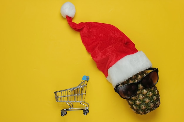 Christmas shopping. pineapple dressed in santa hat with sunglasses and shopping trolley on yellow background. top view.