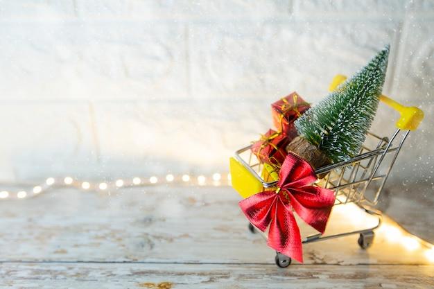 Christmas shopping season concept  mini shop cart trolley full of gift box on brick background