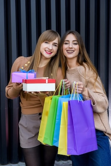Christmas shopping. two happy women with colorful gift bags posing after shopping