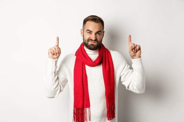 Concetto di shopping natalizio e vacanze invernali. ragazzo dispiaciuto e scettico che si lamenta, puntando il dito su un cattivo prodotto, in piedi su uno sfondo bianco.