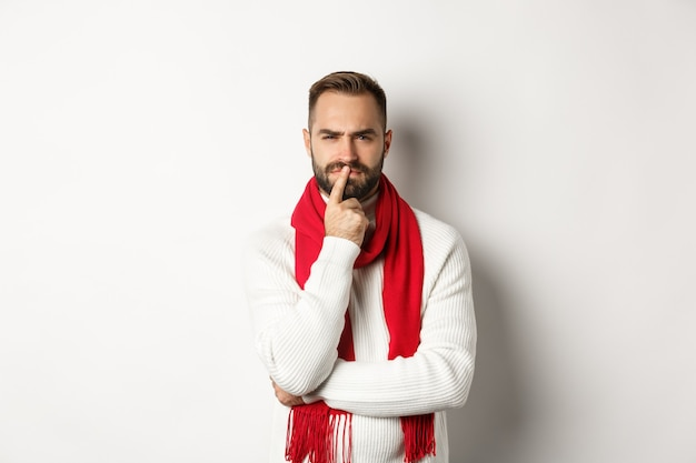 Christmas shopping and winter holidays concept. serious looking bearded guy thinking, squinting and pondering ideas, standing against white background