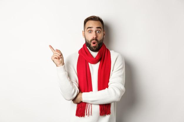 Concetto di shopping natalizio e vacanze invernali. sorpreso ragazzo barbuto che controlla gli sconti del nuovo anno, puntando il dito a sinistra nello spazio vuoto, in piedi su sfondo bianco