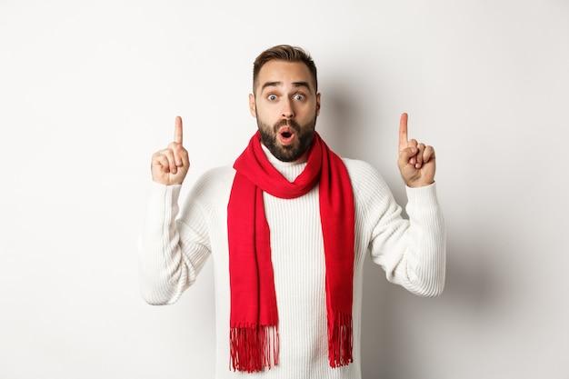 Concetto di shopping natalizio e vacanze invernali. modello maschio sorpreso con la barba che punta le dita verso l'alto, dicendo wow, guardando impressionato dalla telecamera, sfondo bianco