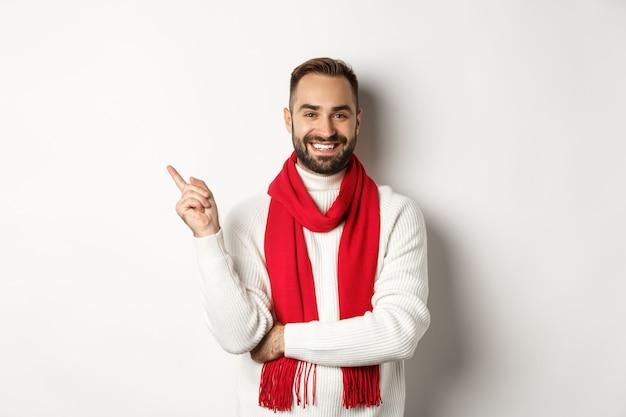 Concetto di shopping natalizio e vacanze invernali. giovane con la barba che punta il dito a sinistra, mostrando la pubblicità del nuovo anno, in piedi su sfondo bianco con sciarpa rossa e maglione