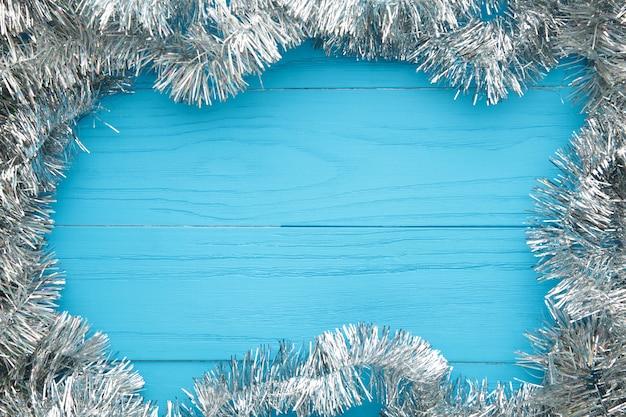Сусаль рождества серебряная на голубой деревянной предпосылке. у этого есть обтравочный контур. вид сверху.