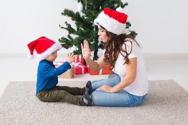 크리스마스, 편부모, 휴일 개념 - 집에서 어머니를 위한 크리스마스 선물을 들고 있는 귀여운 소년.