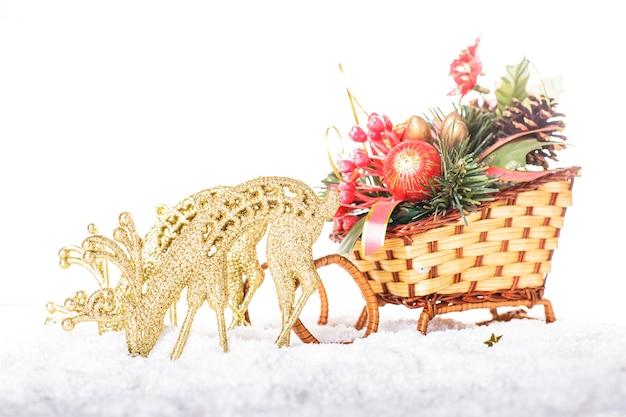 Рождественские сани с декором и оленями на снегу