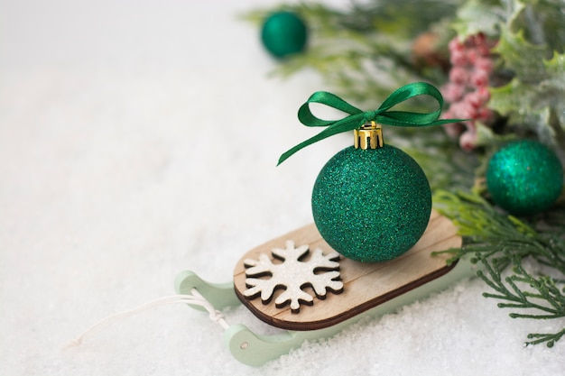 Christmas sleigh with green bauble on snow. abstract winter greeting card.