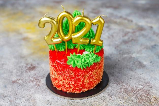 クリスマスツリー、サンタクロース、キャンドルの甘い数字で飾られたクリスマスの小さなケーキ。