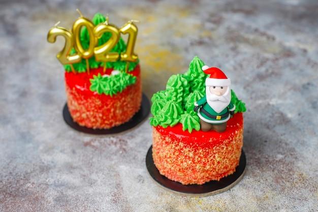 Рождественский торт украшен сладкими фигурками елки, санта клауса и свечей.