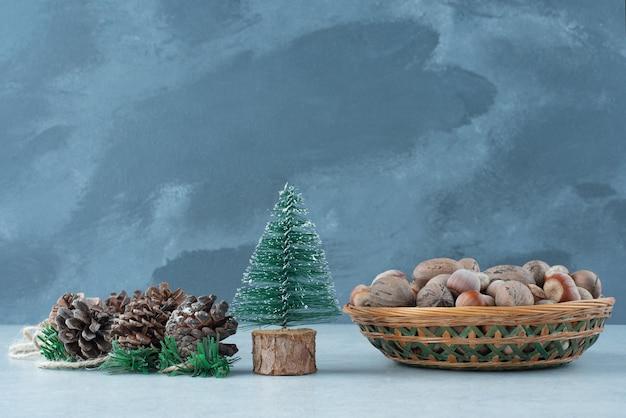 大理石の背景にナッツのバスケットとクリスマスの小さな木。高品質の写真