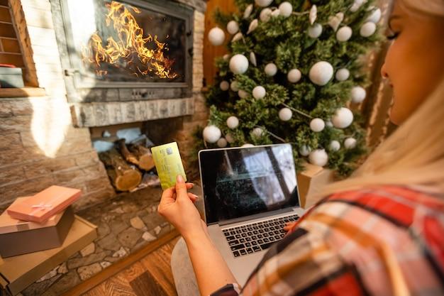 Рождество: улыбающаяся женщина, использующая кредитную карту для покупок в интернете