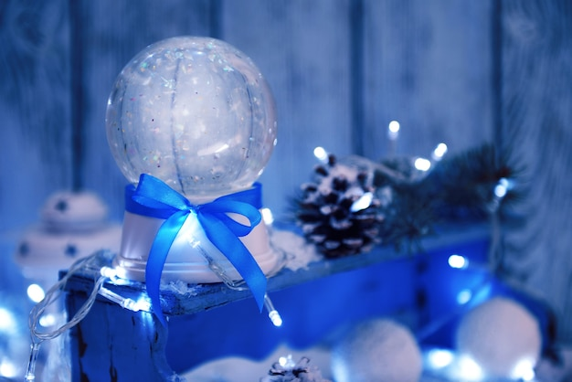 Christmas snow globe with blue bow in snow on wooden background