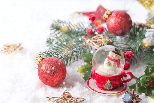 Рождественский снежный шар с сосновыми ветвями и праздничными украшениями на снежном столе. рождество или новый год концепция