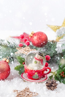 Christmas snow globe with pine branches and festive decorations on snow table. christmas or new year concept