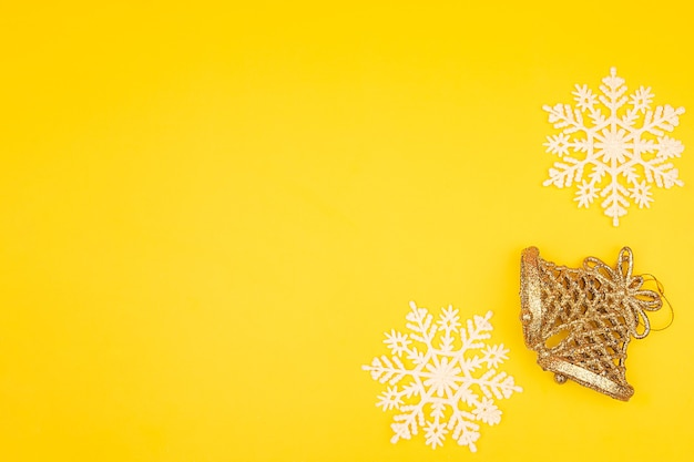 Christmas snowflakes and golden bells on a yellow
