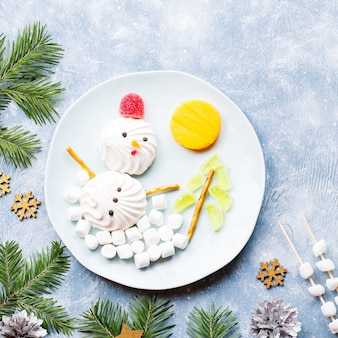 Christmas snowman made of marshmallow and fruit jelly on a plate with fir branches and decorations. top view, copy space