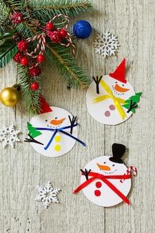 木製のテーブルにクリスマス雪だるまの陽気な贈り物子供のための手作りの工芸品