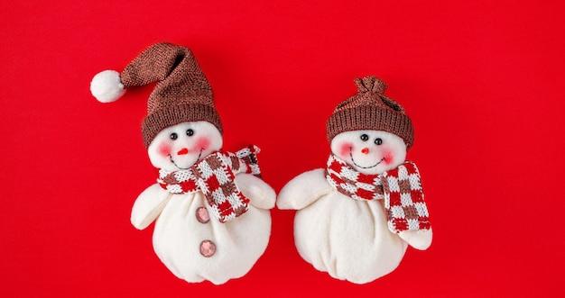 Рождественские игрушки снеговика на красном фоне
