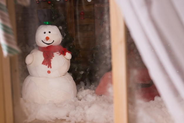 Christmas snowman viewed through a frosted window with open curtain standing in the winter snow outside in the darkness