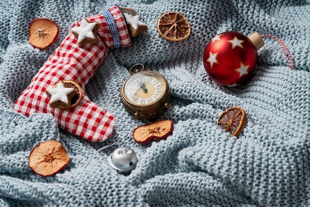 Рождественский носок, наполненный звездным печеньем и украшенный сушеными апельсинами, часами и елочной игрушкой поверх синего пледа. уютная рождественская концепция